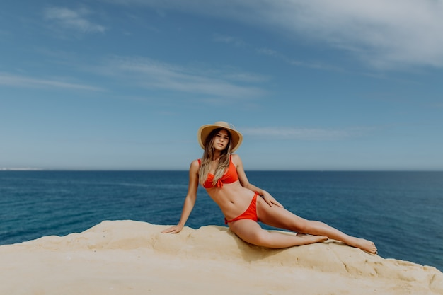 Young sexy woman in red bikini and straw hat lying on the rock edge