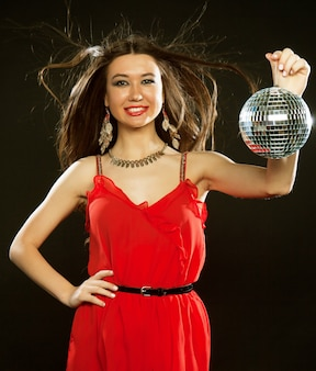 Young sexy woman in red dres keeping disco ball