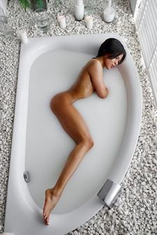 若いセクシーな女性、ミルクとお風呂でリラックス。バスタブの女性、スパの美容とヘルスケア、バスルームのウェルネストリートメント、背景の小石とキャンドル