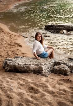 Молодая сексуальная женщина, сидящая на большой скале на песчаном берегу моря