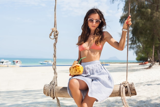 Young sexy woman sitting on swing on tropical beach, summer vacation, fashion style, skirt, bikini top, drinking coconut cocktail, smiling, relaxing
