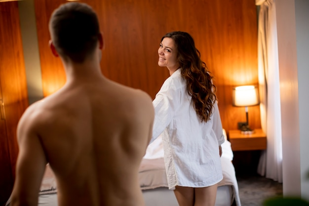 Young sexy woman taking young man to bed at home