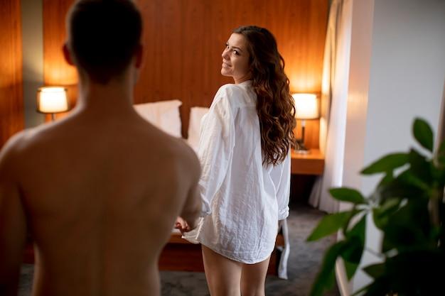 Молодая сексуальная женщина принимает молодого человека в постель дома