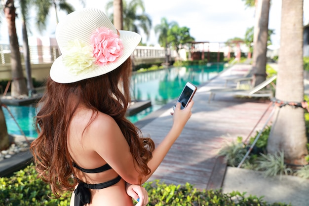 Young and sexy woman using cell phone while on holiday vacation near swimming pool