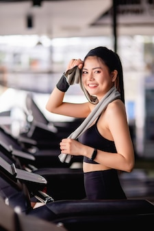 Young sexy woman wearing sportswear, sweat-proof fabric and smartwatch use towel wipe sweat on forehead during workout in modern gym, smile , copy space