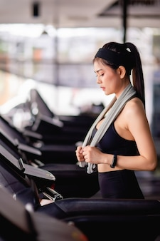 Young sexy woman wearing sportswear, sweat-proof fabric and smartwatch walking on treadmill warm up before run to workout in modern gym, copy space
