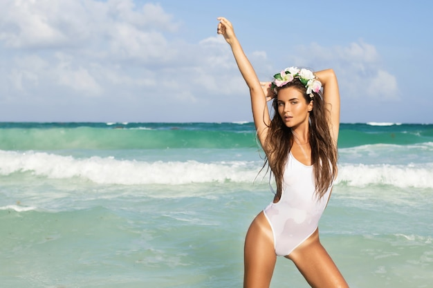 Young sexy woman wearing white swimsuit is posing on the beach