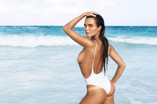 흰색 수영복을 입고 젊은 섹시한 여자가 해변에서 포즈