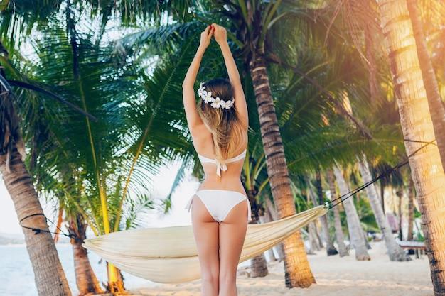 Giovane donna sexy in costume da bagno bikini bianco in posa sulla spiaggia tropicale, sfondo di palme, hawaii, fiori nei capelli, corpo sensuale e snello, soleggiato, vista dal retro, godendo le vacanze, viaggiando sull'isola