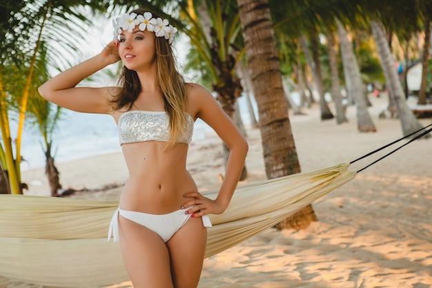 Giovane donna sexy in costume da bagno bikini bianco in posa sulla spiaggia tropicale, palme, hawaii, fiori nei capelli, sensuale, corpo snello, soleggiato, godendo le vacanze, viaggiando sull'isola