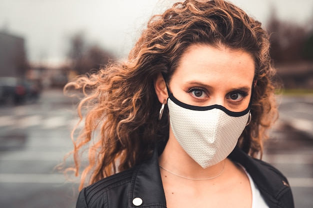 駐車場に白いマスクを持つ若いセクシーな女性
