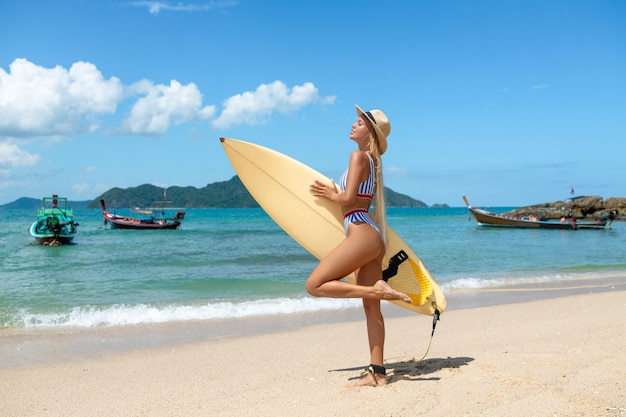 Young sexy woman with blonde hair and sportive tanned body, posing with surf board  beach in sunny summer day, ready   surfing. wearing stylish bikini. positive emotions