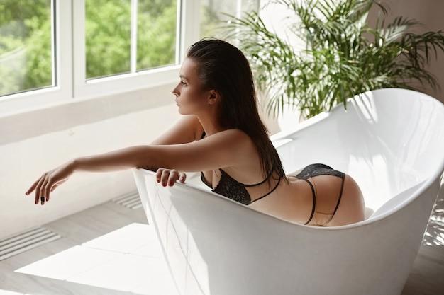 バスタブでポーズをとるベージュのランジェリーで素晴らしい体型を持つ若いセクシーな女性。浴室のインテリア、スパトリートメントでモデルの女の子の完璧なボディ