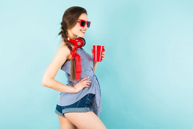 Young sexy woman with headphones and cup