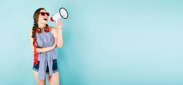 Young sexy woman with headphones and loudspeaker