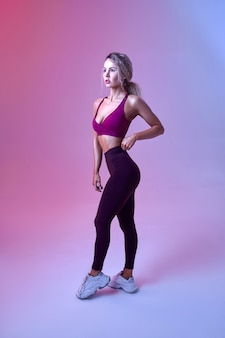 Young sexy woman with slim body poses in studio, neon background. sportswoman at the photo shoot, sport concept, active lifestyle motivation