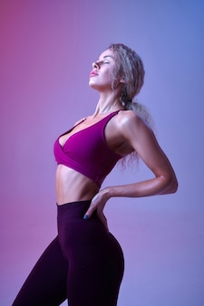 Young sexy woman with slim body poses in studio, neon background. sportswoman at the photo shoot, sport concept, active lifestyle