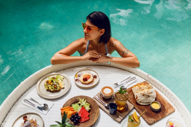 プライベートプールで朝食をとり水着で入れ墨を持つ若いセクシーな女性。コーヒーを飲みながら果物を食べるプールでリラックスした女の子。ホテルのプールサイドにあるフルーツプレート、スムージーボウル。