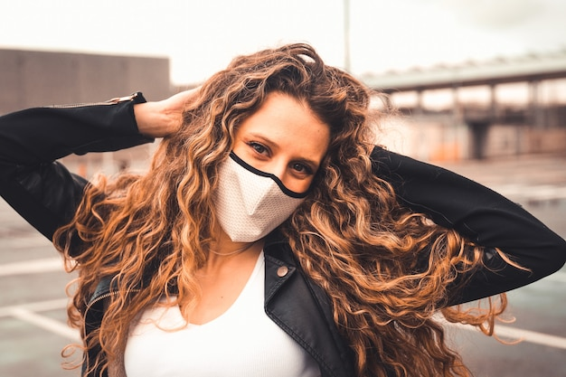 Young sexy woman with a white mask on a parking lot