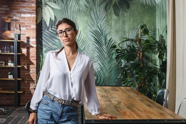 나무 테이블에 의해 현대 아파트에 서 있는 안경에 젊은 섹시 한 여성