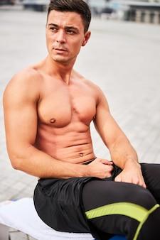 若い格好良いトップレスの男は、街のスポーツグラウンドでプロのベンチで腹筋クランチをしています