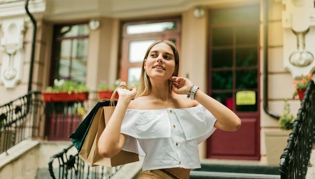 최신 유행의 옷을 입고 젊은 sharming shopaholic 여자