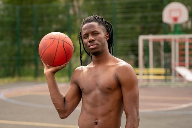 バスケットボールコートにボール立って若い上半身裸のアフリカの筋肉の運動選手