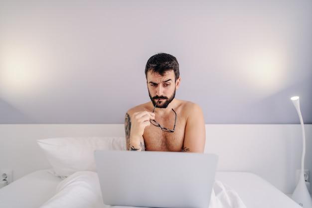 若い上半身裸のひげを生やした入れ墨男の寝室のベッドの上に座って、ラップトップを使用して