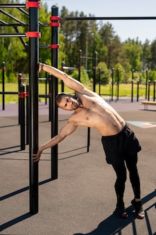 若い上半身裸のボディービルダー側曲げと運動中にスポーツ施設のバーで保持