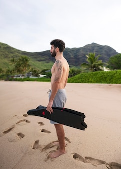 Young shirtless man on the beach with scuba diving equipment