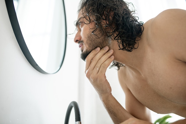 Young shirtless man bending over sink in front of mirror while touching his beard before shaving it