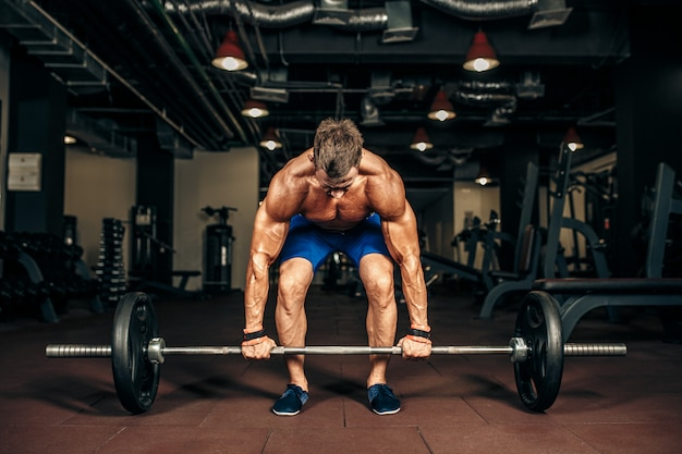 Young shirtless man doing deadlift exercise at gym.