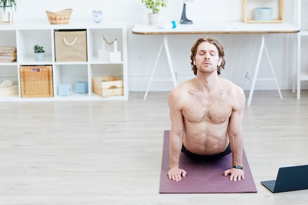 Young shirtless man doing stretching exercises on exercise mat in the living room at home