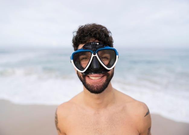 Молодой человек без рубашки на пляже с оборудованием для подводного плавания
