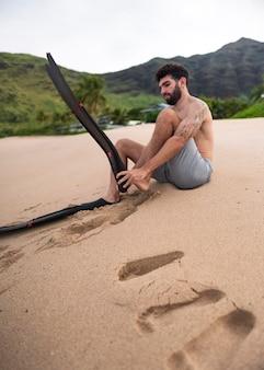 スキューバダイビング器材とビーチで若い上半身裸の男