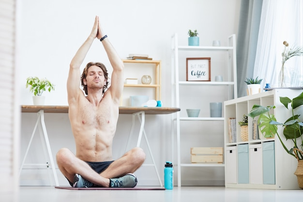 Young shirtless man sitting on exercise mat and doing breathing exercises in the living room