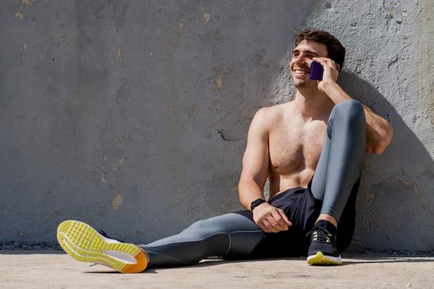 Молодой человек без рубашки разговаривает по мобильному телефону после тренировки улыбается веселый