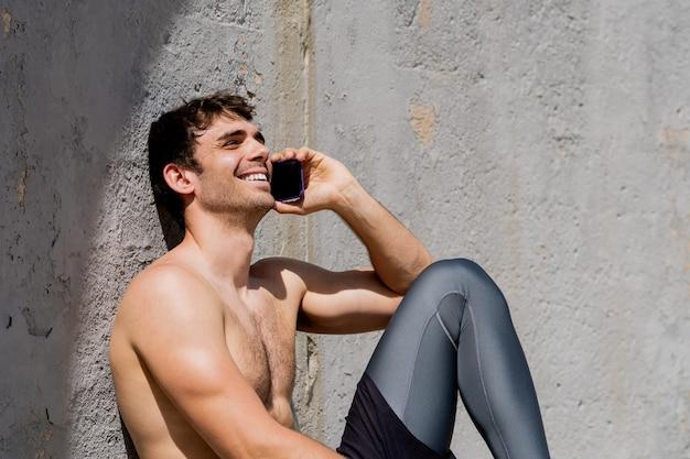 쾌활 한 미소 훈련 후 모바일에 얘기 하는 젊은 벗은 남자