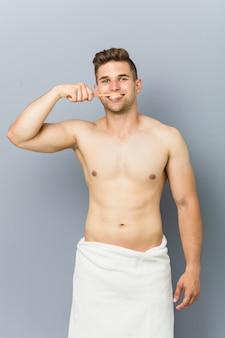 歯を洗う若い上半身裸の男。