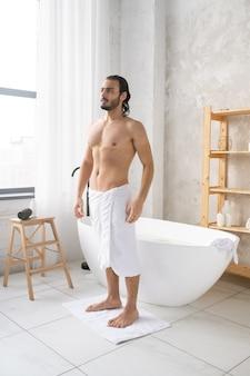 거품으로 뜨거운 목욕을 한 후 작은 양탄자에 서있는 엉덩이에 부드러운 흰색 수건을 가진 젊은 벗은 남자