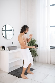 Молодой человек без рубашки с белым полотенцем на бедрах и портативным беспроводным bluetooth-динамиком танцует в ванной после утренних гигиенических процедур