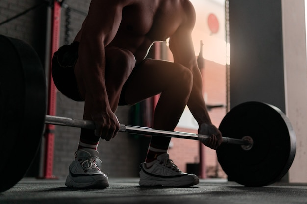 Young shirtless muscle athlete preparing to do deadlift at a crossfit gym