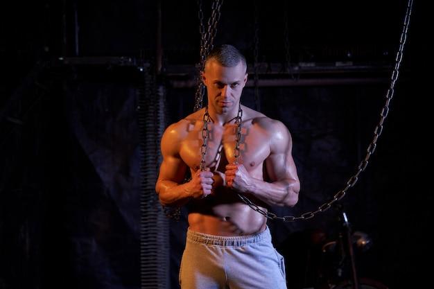金属チェーンの間に立って、カメラ、コピースペースを真剣に見ている若い上半身裸の筋肉質の男