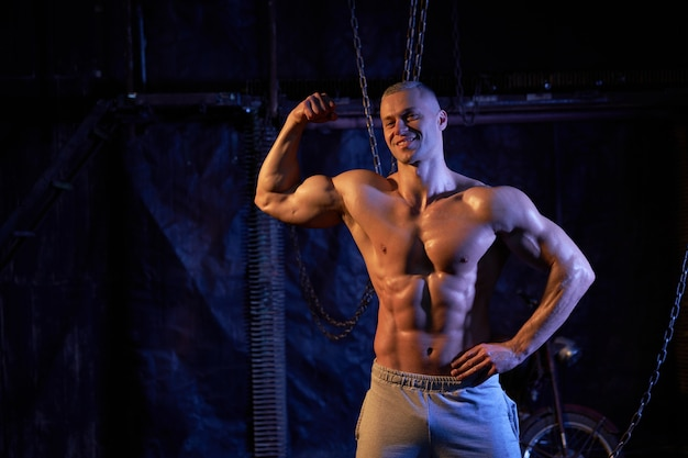 Young shirtless muscular man standing among metal chains, looking seriously at camera, copy space with his back to the camera shows biceps