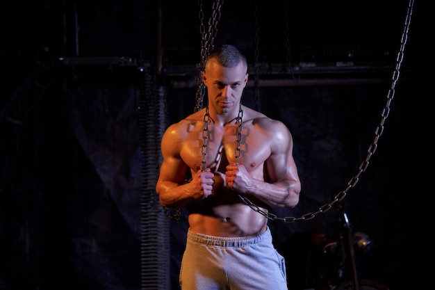 Young shirtless muscular man standing among metal chains, looking seriously at camera, copy space