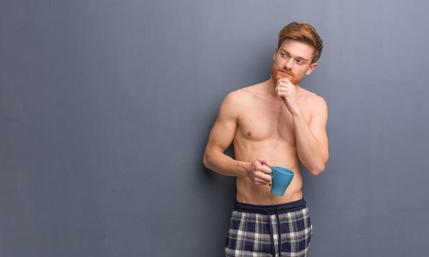 Молодой рыжий мужчина без рубашки сомневается и смущается. он держит кофейную кружку.