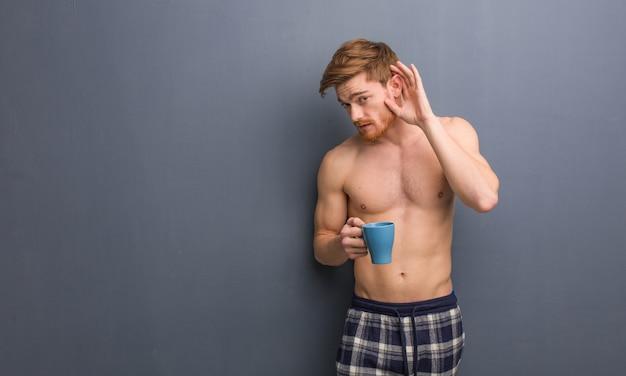 Молодой рыжий мужчина без рубашки пытаются слушать сплетни. он держит кофейную кружку.