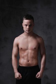 Молодой сексуальный мужчина без рубашки позирует