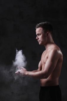 若い上半身裸のセクシーな男のポーズ