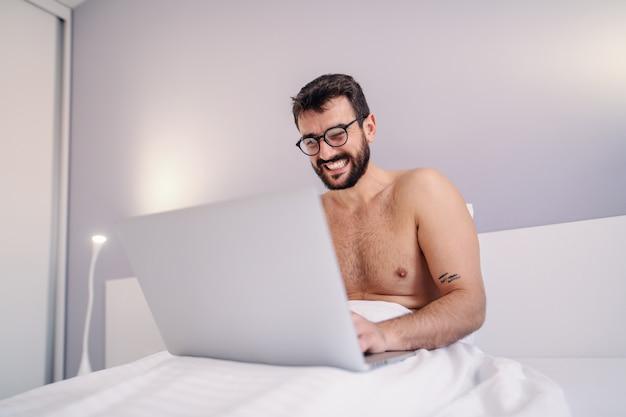 若い上半身裸の笑みを浮かべてひげを生やした入れ墨男の寝室のベッドの上に座って、ラップトップを使用して